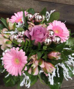Růžová zimní kytička dozdobená baňkami.